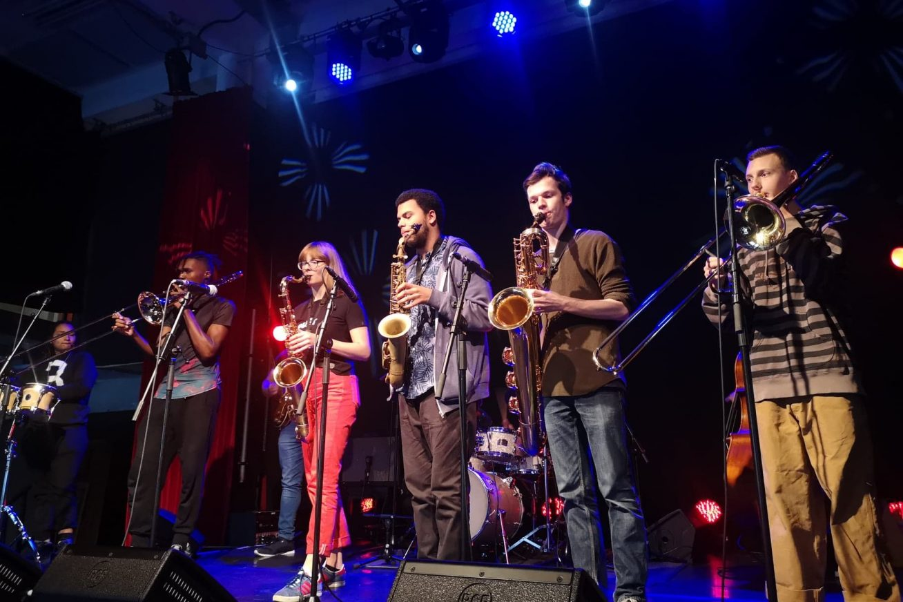 A group of jazz musicians play an assortment of instruments on stage