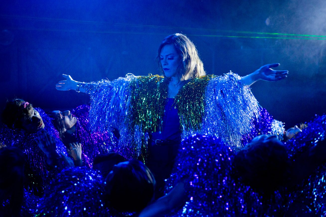 A transgender white woman with long brown hair dances with her arms out to the sides under a striking blue light. Her body is covered in a costume that is made up of glittery tassels in this still from A Fantastic Woman.