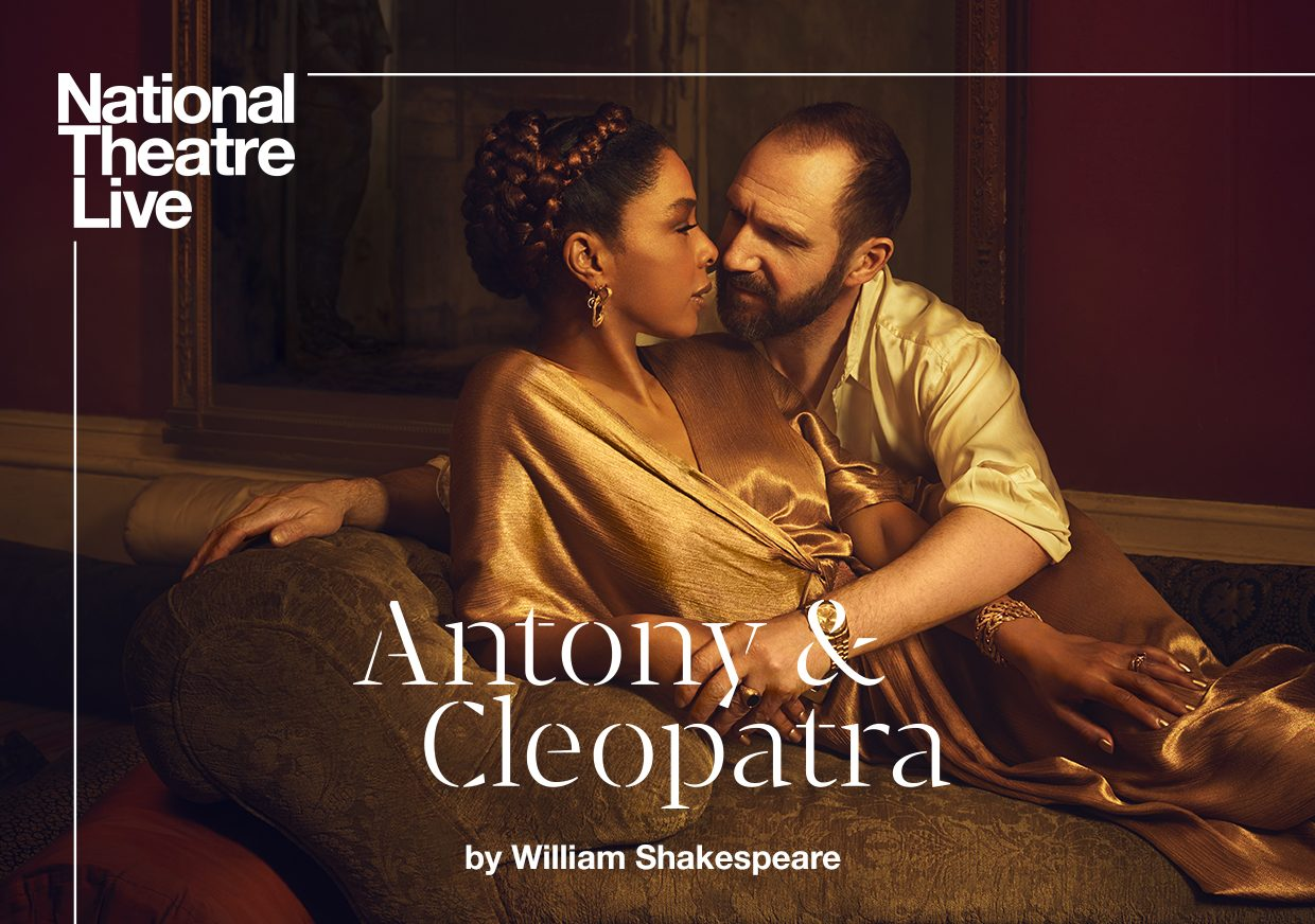 A reclining man and woman lean into each other as if they are about to kiss in this oil-painting styled piece of artwork from NT Live: Antony & Cleopatra.