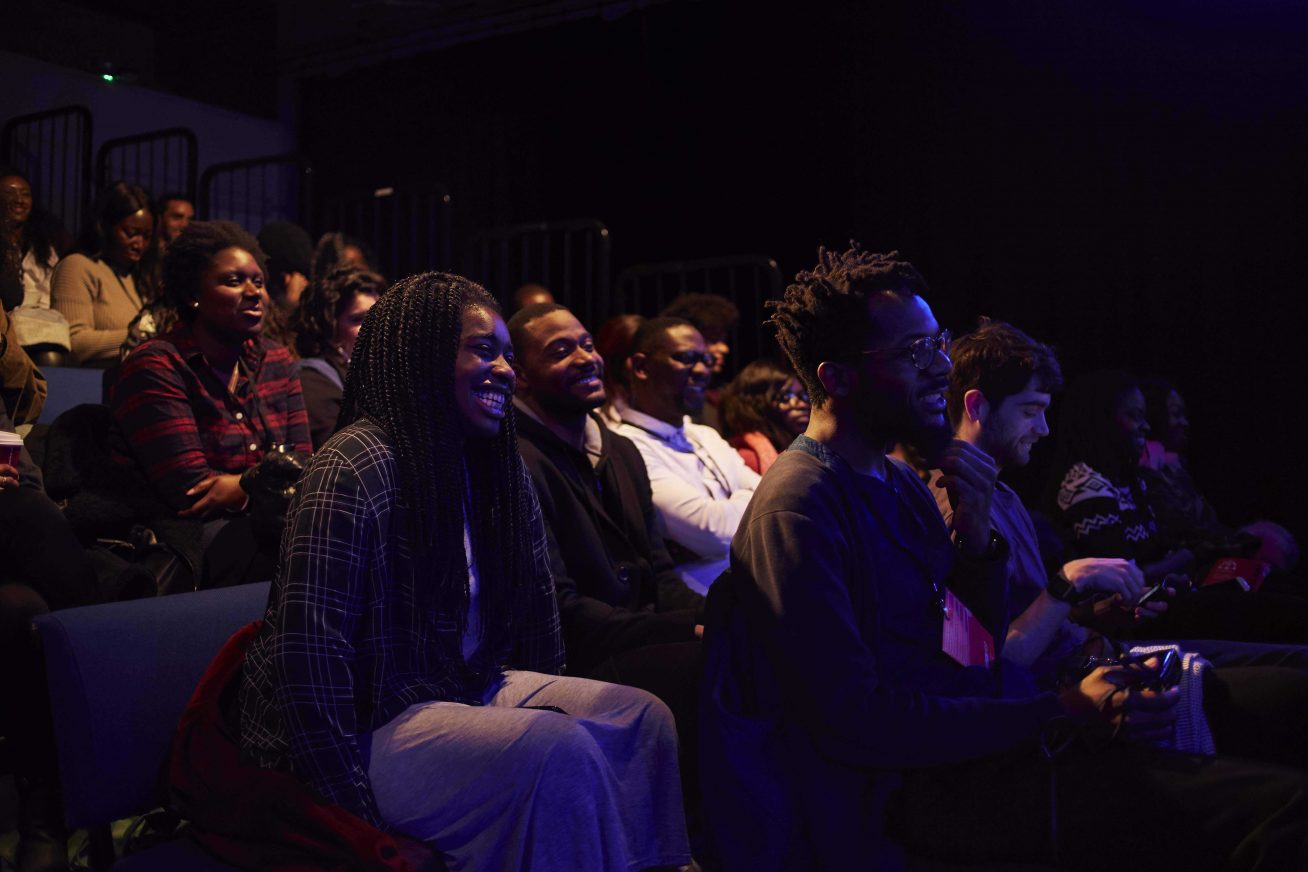 A picture of a very multi-cultural audience in raised theatre-style seats. They smile happily, and the front two rows are bathed in a slight purple glow in this image from Afrotech Fest.