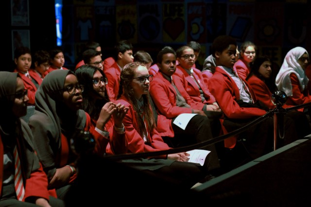 School children, dressed in uniform, are seated in a cinema screen watching a film.