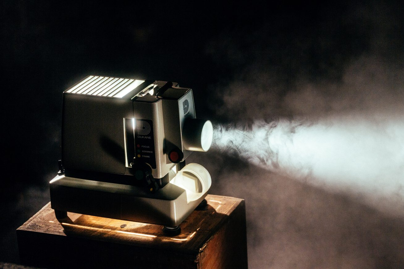An old-fashioned film projector sits on a small wooden table, it shines light into a dark, smokey room from left to right on this page about unique weddings at Rich Mix.