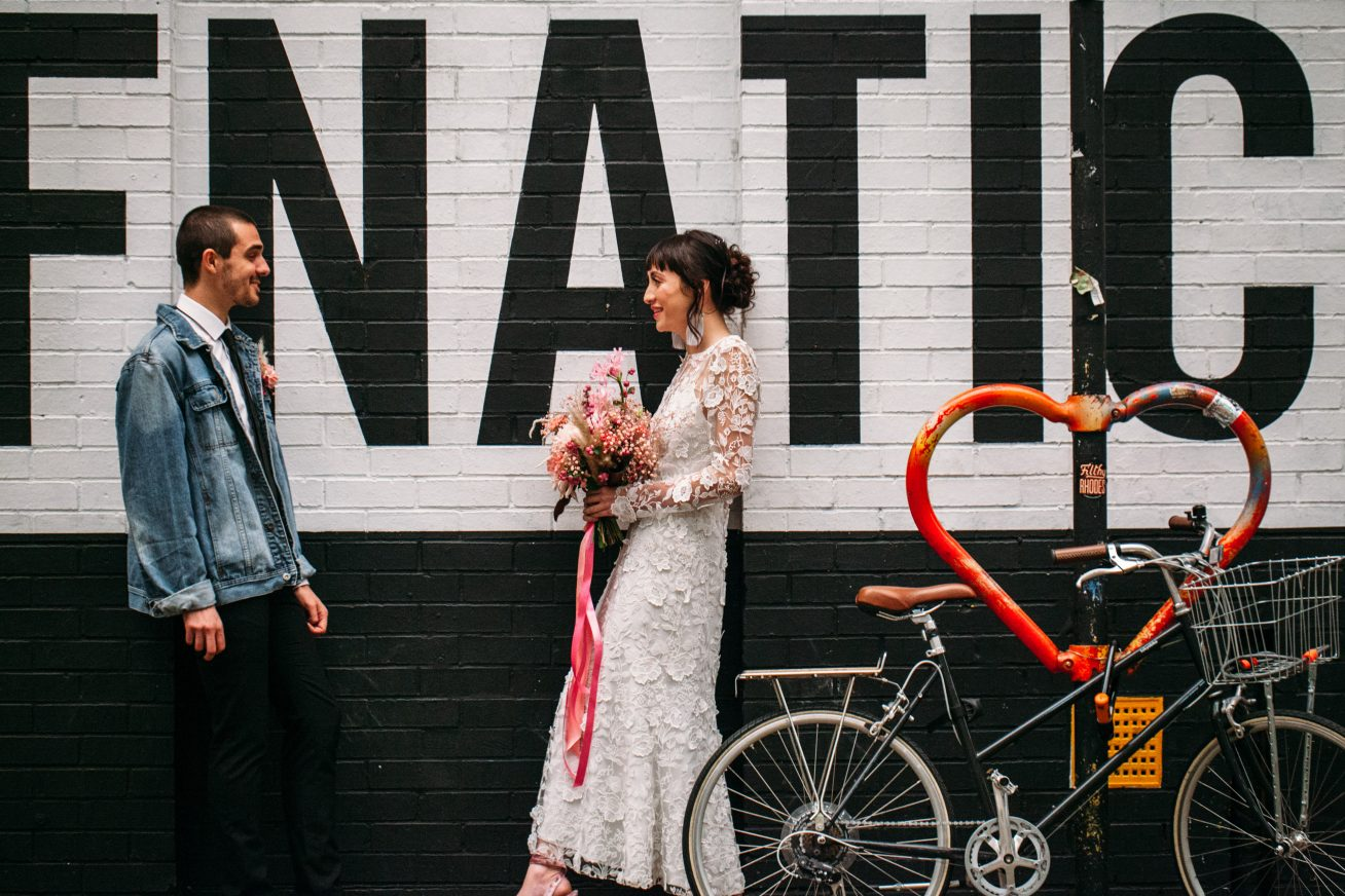 A young, alternative goom in a denim suit jacket and black trousers stands opposit an alternative bride in a white lace dress. In her hands is a bright, pink bouquet in this image advertising wedding, reception, engagement party and anniversary hires of Rich Mix.