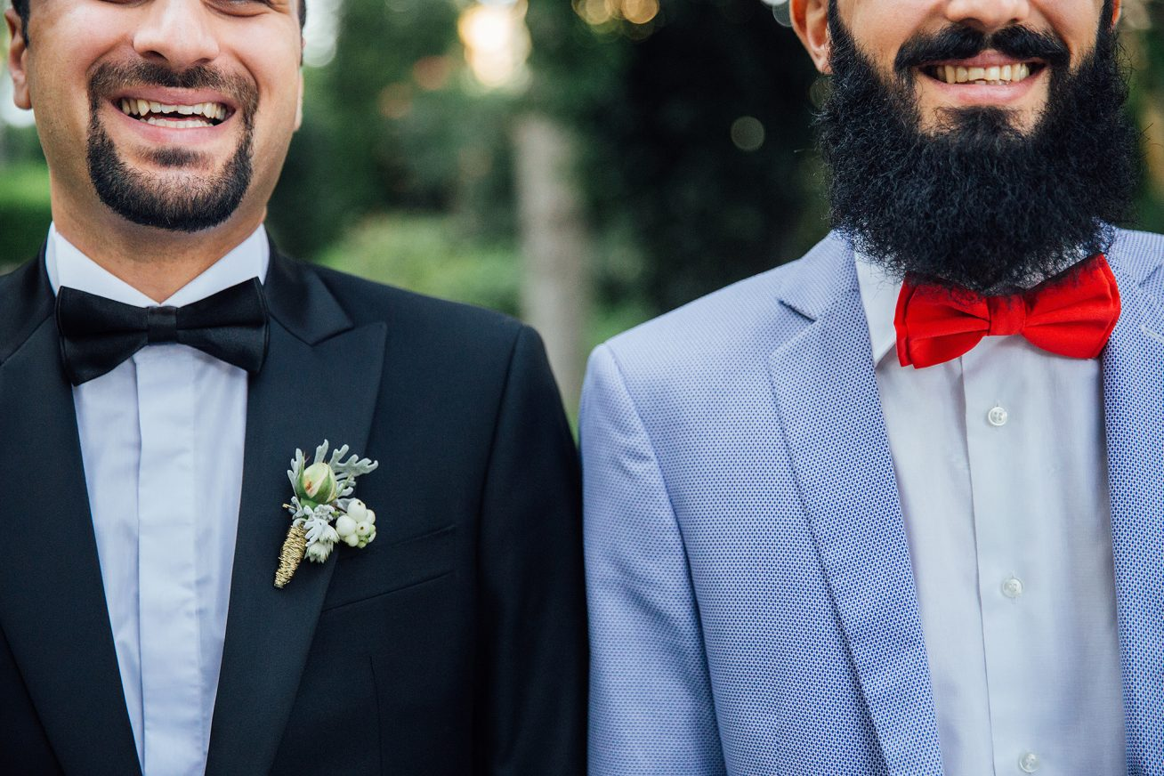 We see two grooms from the cheekbone down to the waist, dressed in smart-casual, stylish tuxedos. The groom on the right has a big, dark, square beard in this image about Gold Wedding Packages at Rich Mix.