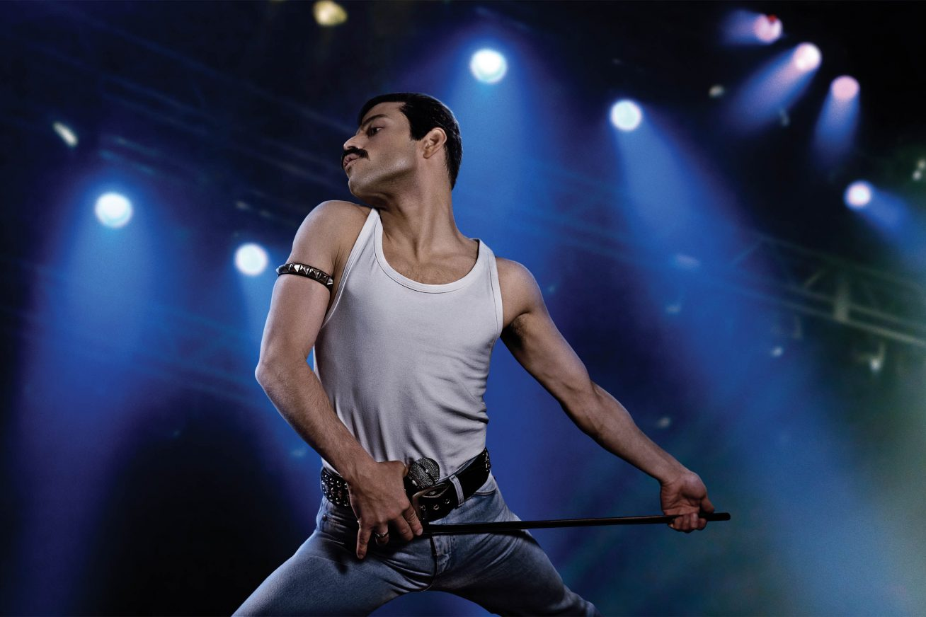 An athletic-looking actor, who looks like Freddie Mercury, plays the air guitar with a microphone stand in this still from Bohemian Rhapsody.