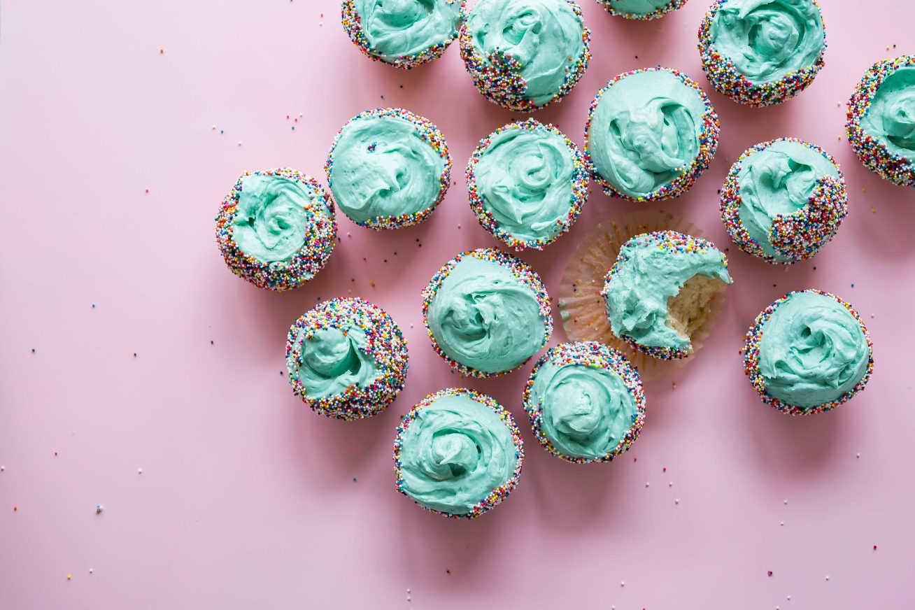 On a light, purple backgroud sits dozens of cupcakes with bright teal icing and multicoloured sprinkles. Towards the right of the picture, one of the cupcakes has a big bite out of it on this page about bespoke wedding services provided at Rich Mix.