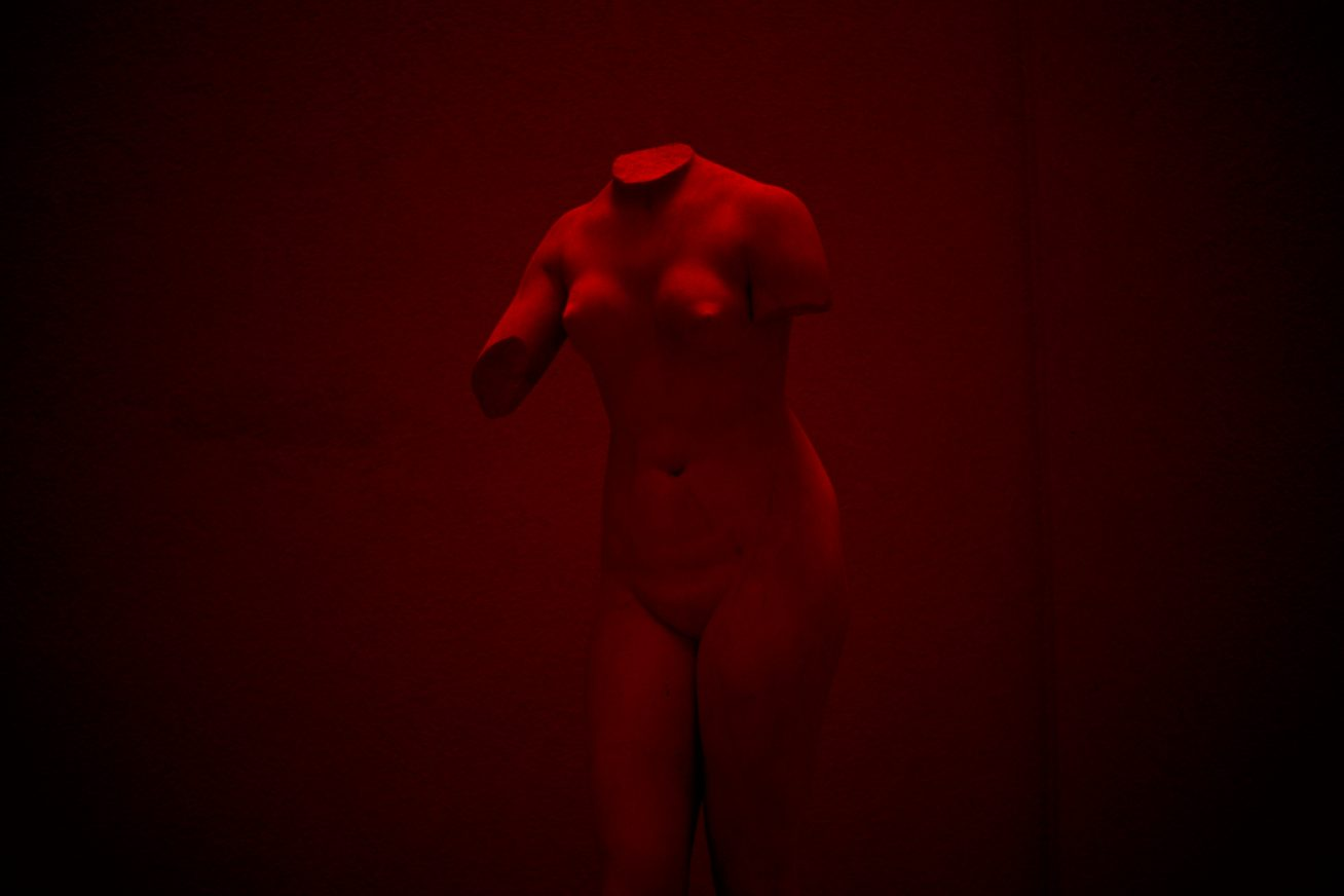 An ancient Greek statue of a naked woman, with no arms or head is light by a dark red light in this image from Vilnius Takes Over festival,