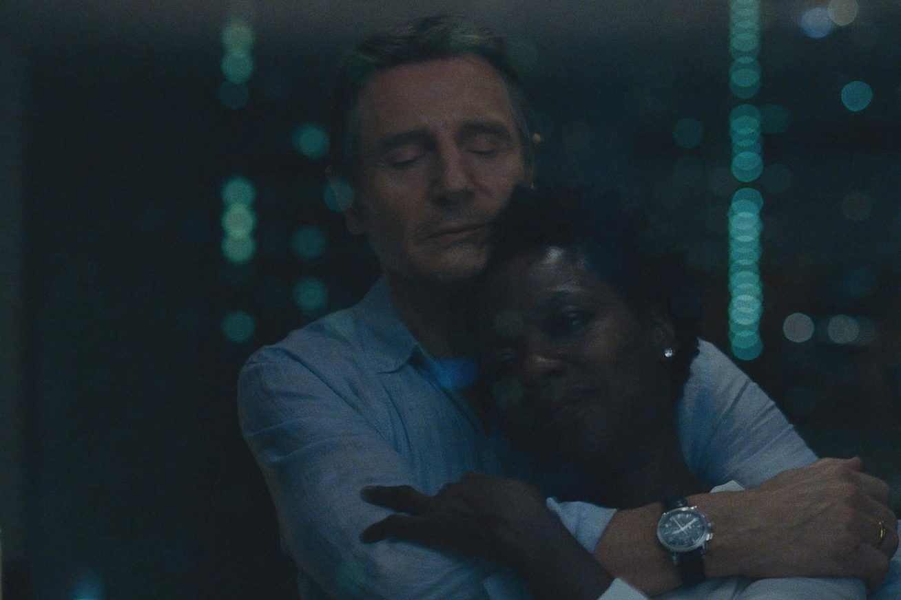 A middle-aged African American woman leans into the affectionate embrace of a middle-aged white man in a light blue shirt in this image from Widows. In the background can be seen blurry, soft green lights.