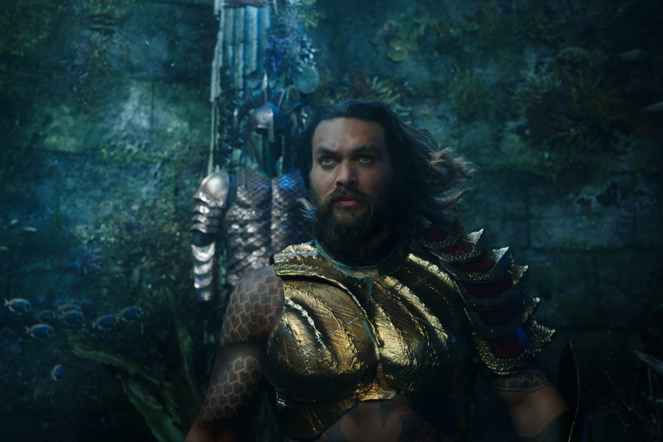 In a magestic underwater setting, a bearded man with long hair walks in ornate golden armour towards the camera in this still from Aquaman.