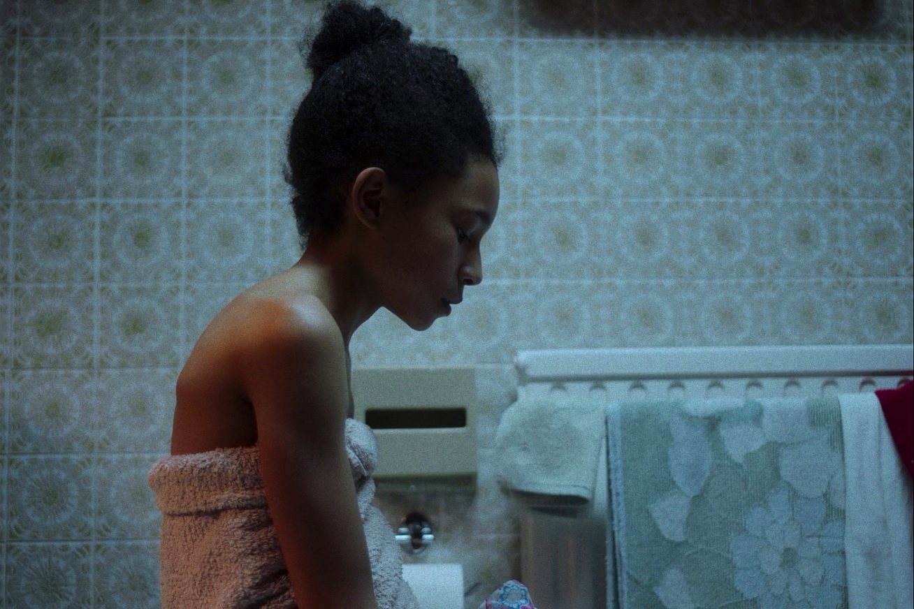 A young girl sits in a bathroom, seemingly on a toilet. She looks down at the floor, and the bathroom fittings look old and beige in this still from London Short Film Festival: Blue Monday.