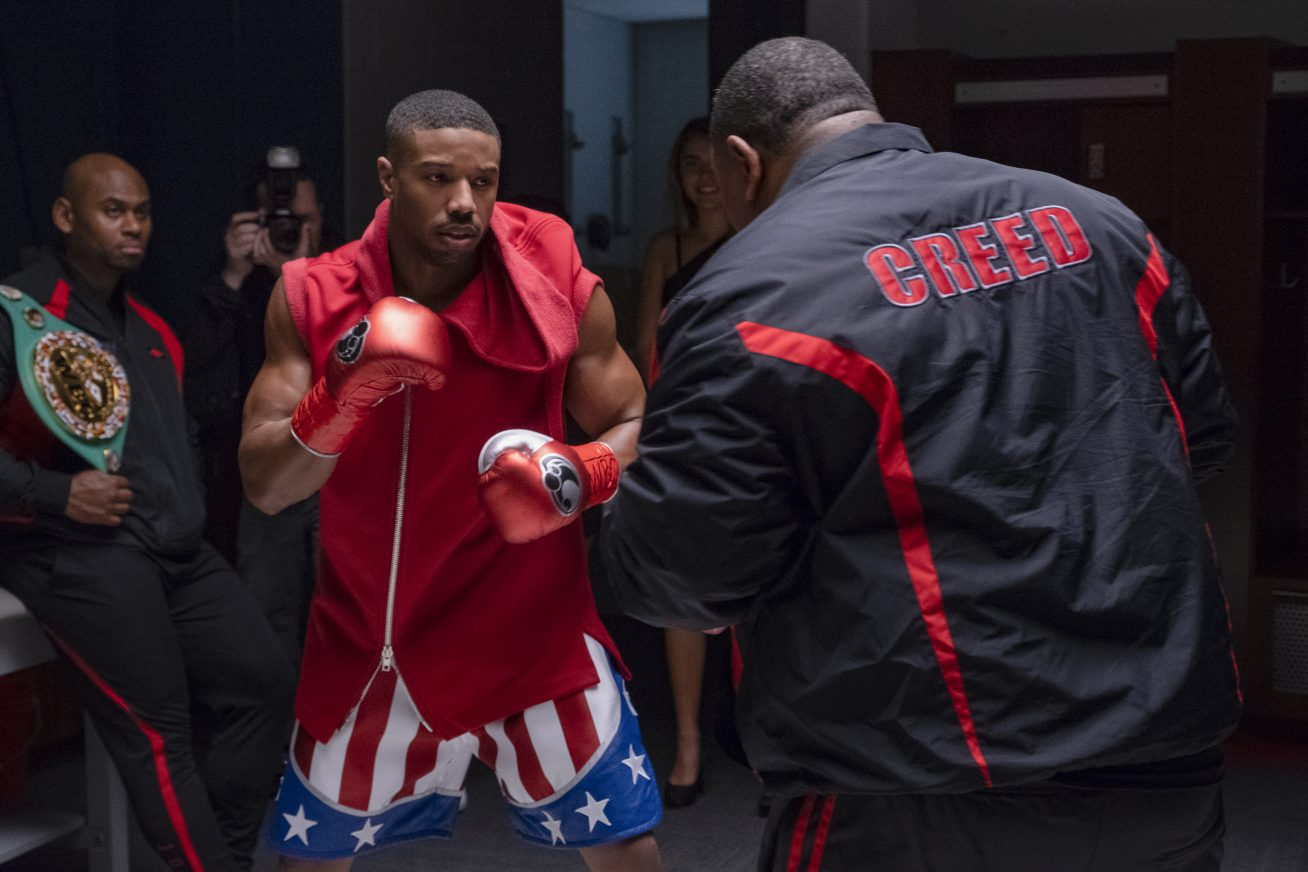 A young African American boxer wearing the colours of the American flag trains with a heavy-set man with the word 'Creed II' on the back of his training gear.