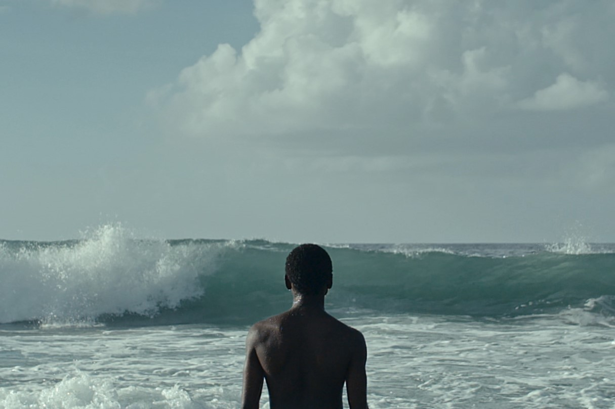 We see a young black man's unclothed upper body, as he stands with his back to us looking out to the crashing waves of an rough ocean in this still from London Short Film Festival: Do You Really Want to Hurt Me.