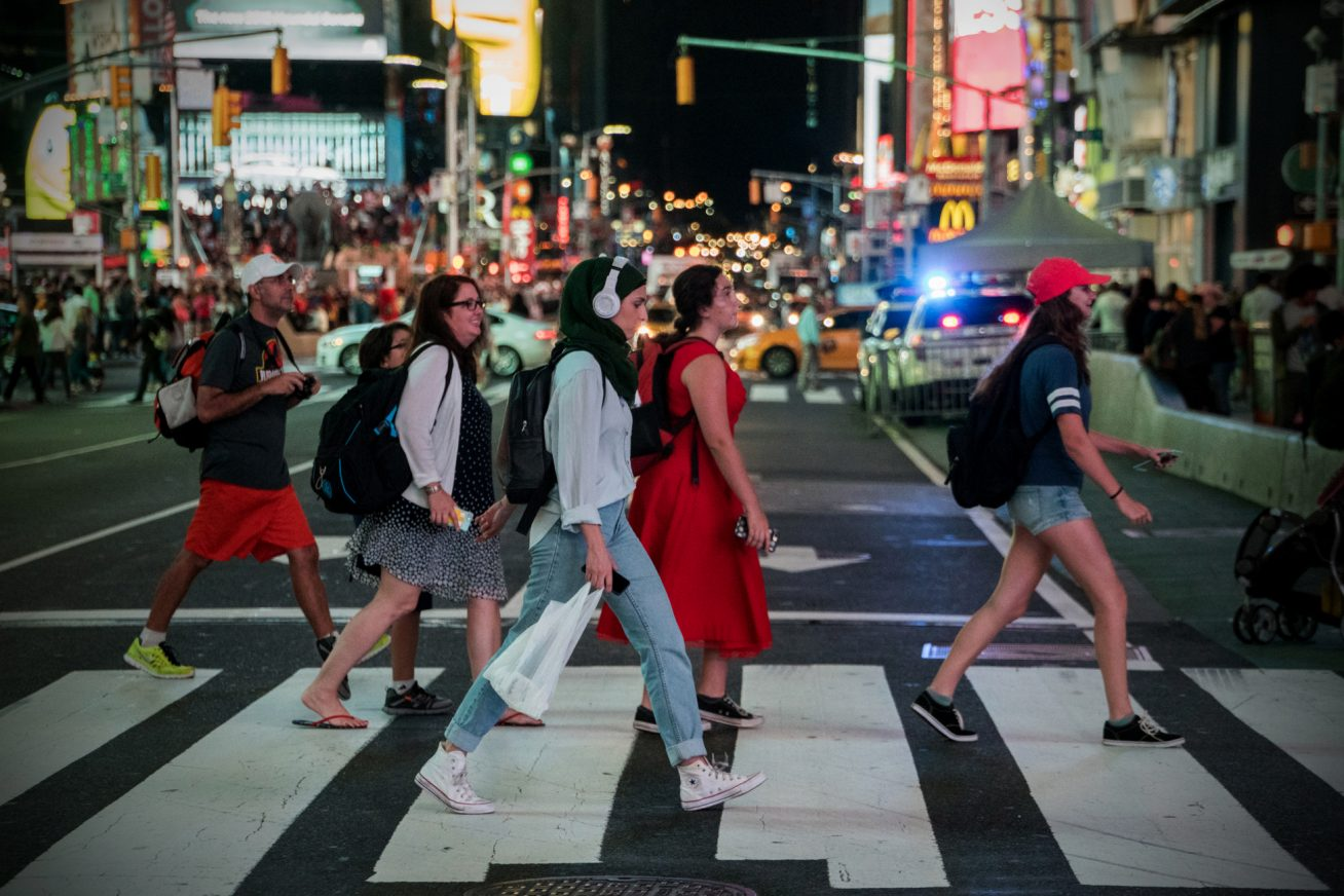 A group of people crosses the road at a busy zebra crossing in downtown New York at night in this still from London Short Film Festival: Fade to Grey.