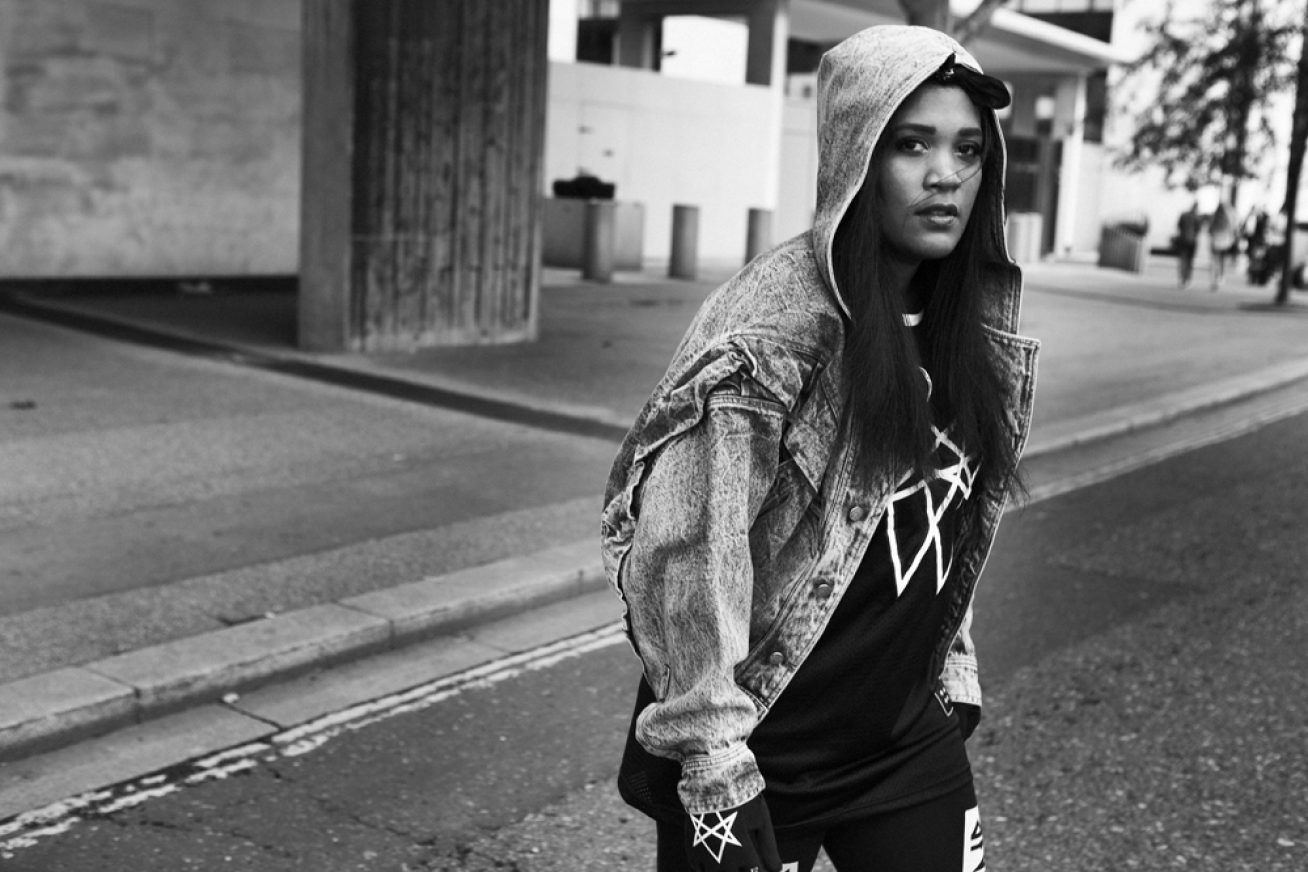 A black and white image of a young woman with long hair in a hoodie. She stands on an empty street in this still from London Short Film Festival: History of Hyperdub.