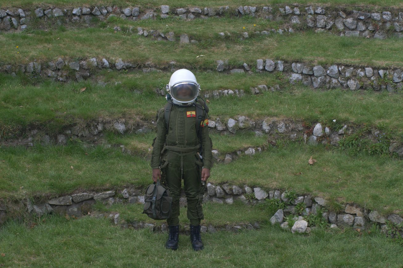 At the foot of a hill shaped into grassy steps, a person stands in an unusual, green astronaut uniform with a briefcase in this still from London Short Film Festival: It Takes a Muscle.