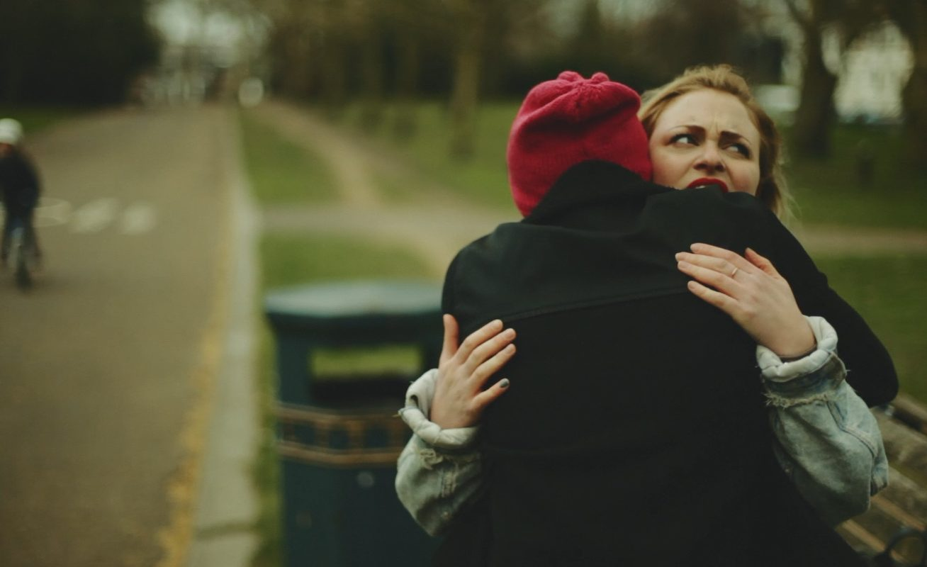 In a public park, a young woman pulls a funny face as someone in a black coat and red beanie hat embraces her in this still from London Short Film Festival: IRL.