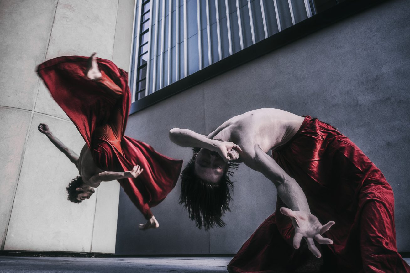 Chinese Arts Now: Red Ink Dance Theatre - Two men jump and dance energetically in a concrete space.