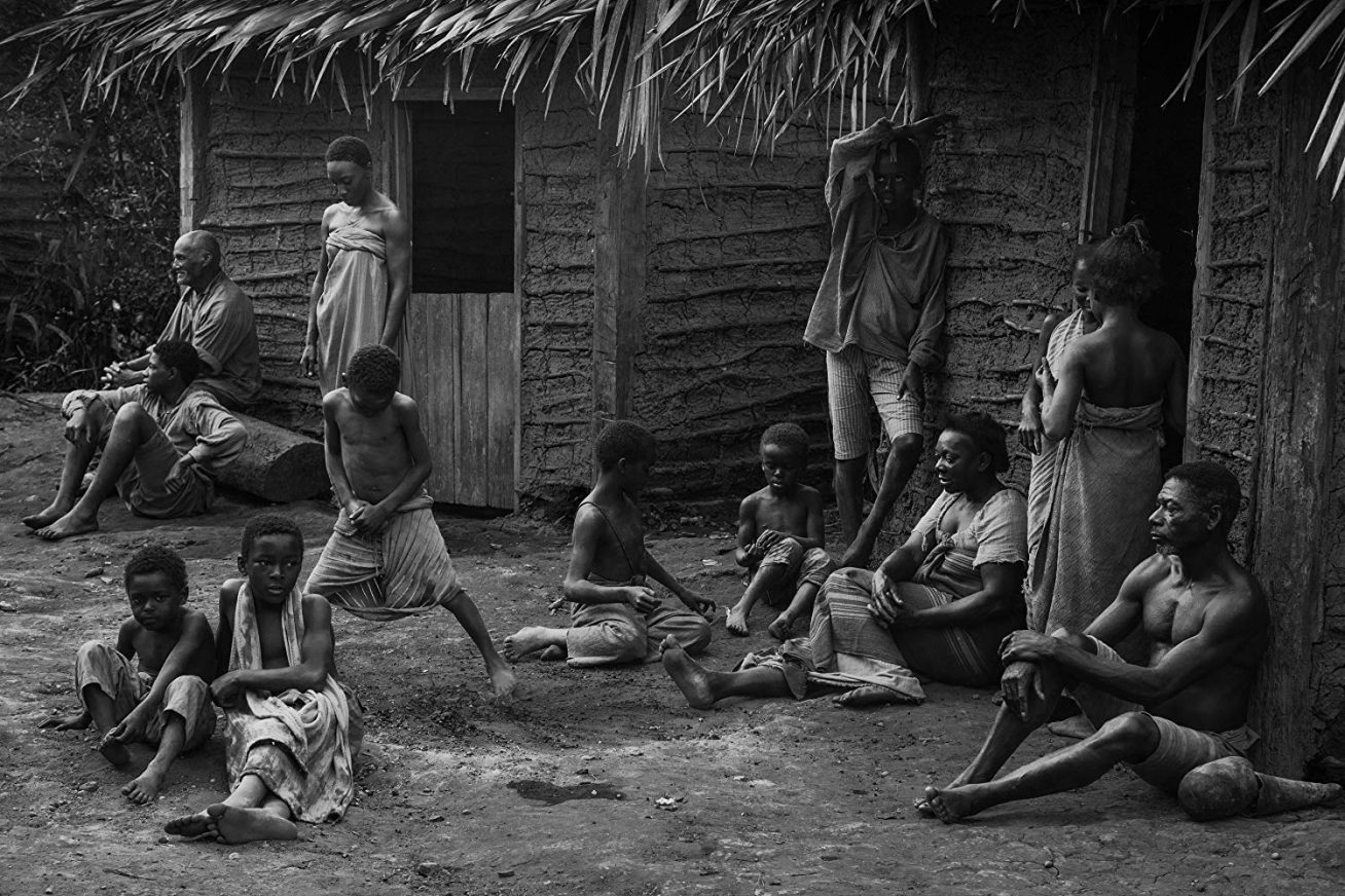 A black-and-white still Vazante of a group of people gathered outside a rustic wooden shack in 19th-century Brazil. Many look poor, even barely dressed.