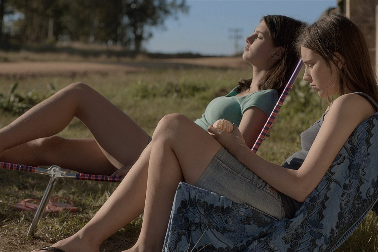Two girls lounge in deck chairs just off a country road under the Brazilian sun in this still from Nalu on the Border.