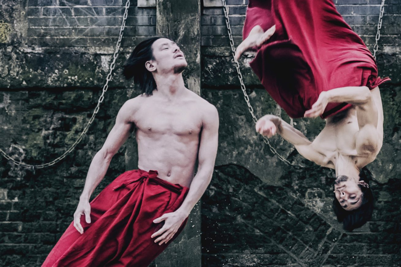 Two men in striking red sarongs take part in energetic dance moves. Their torsos are naked and muscular. The ground is sandy, and behind them sits a brick wall in this image from Chinese Arts Now Festival's Red INK.