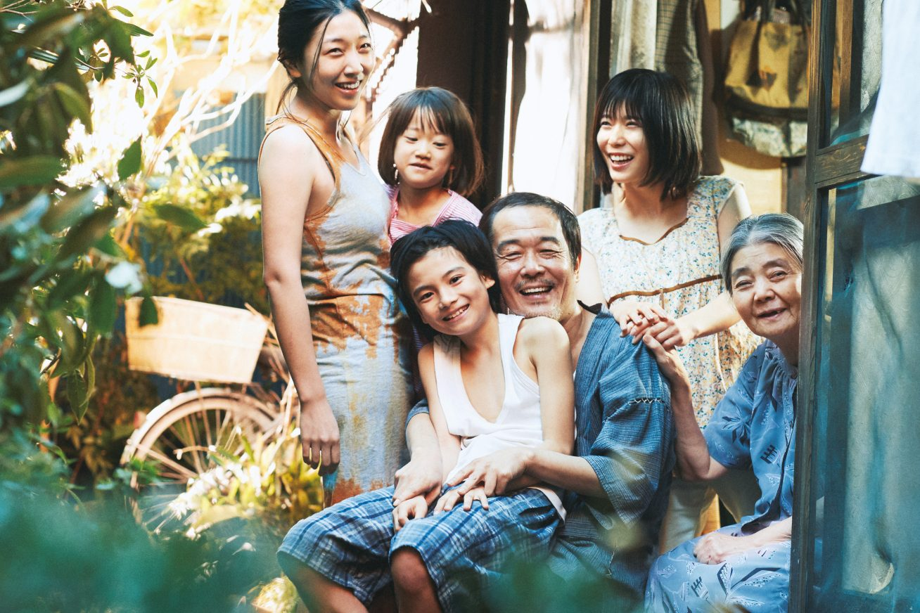 A Japanese family poses for a photo together in a cluttered, colourful back yard, in this still from Shoplifters