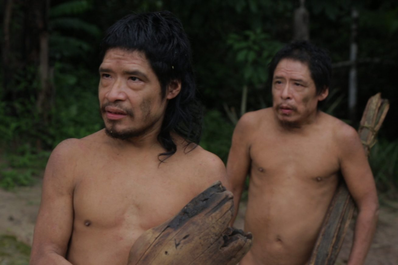 Two bare-chested native Brazilian tribesman carry pieces of wood at the outskirts of a rainforest. They look to the left, past the camera, in this still from Piripkura.