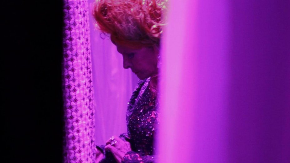 We see a glimpse of a transvestite performer standing ready to go on stage as neon purple curtains hang on either side of him in this still from Divine Divas.