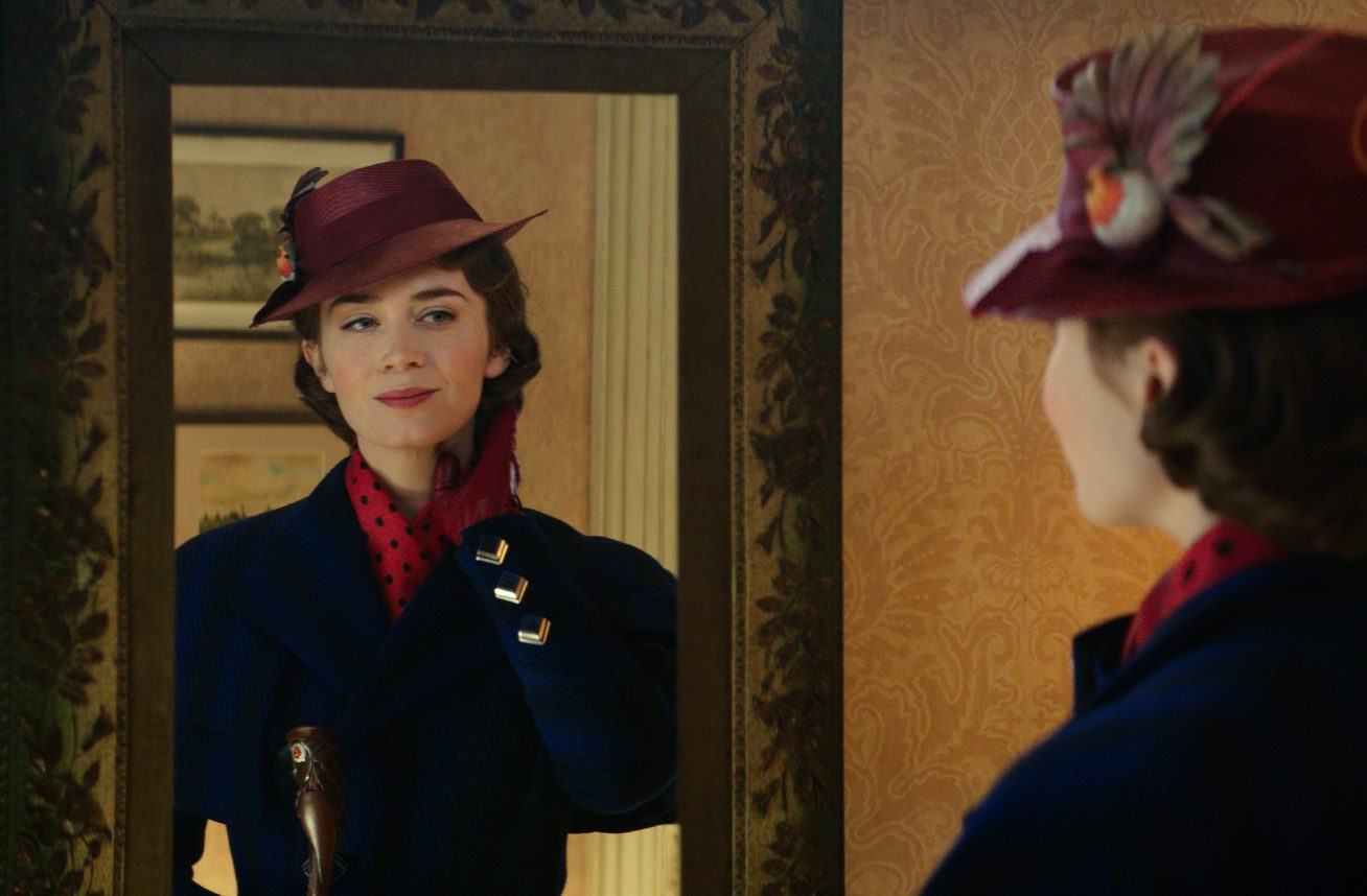 A young white woman in 1930s clothes checks her hair in a mirror in this still from Mary Poppins Returns.