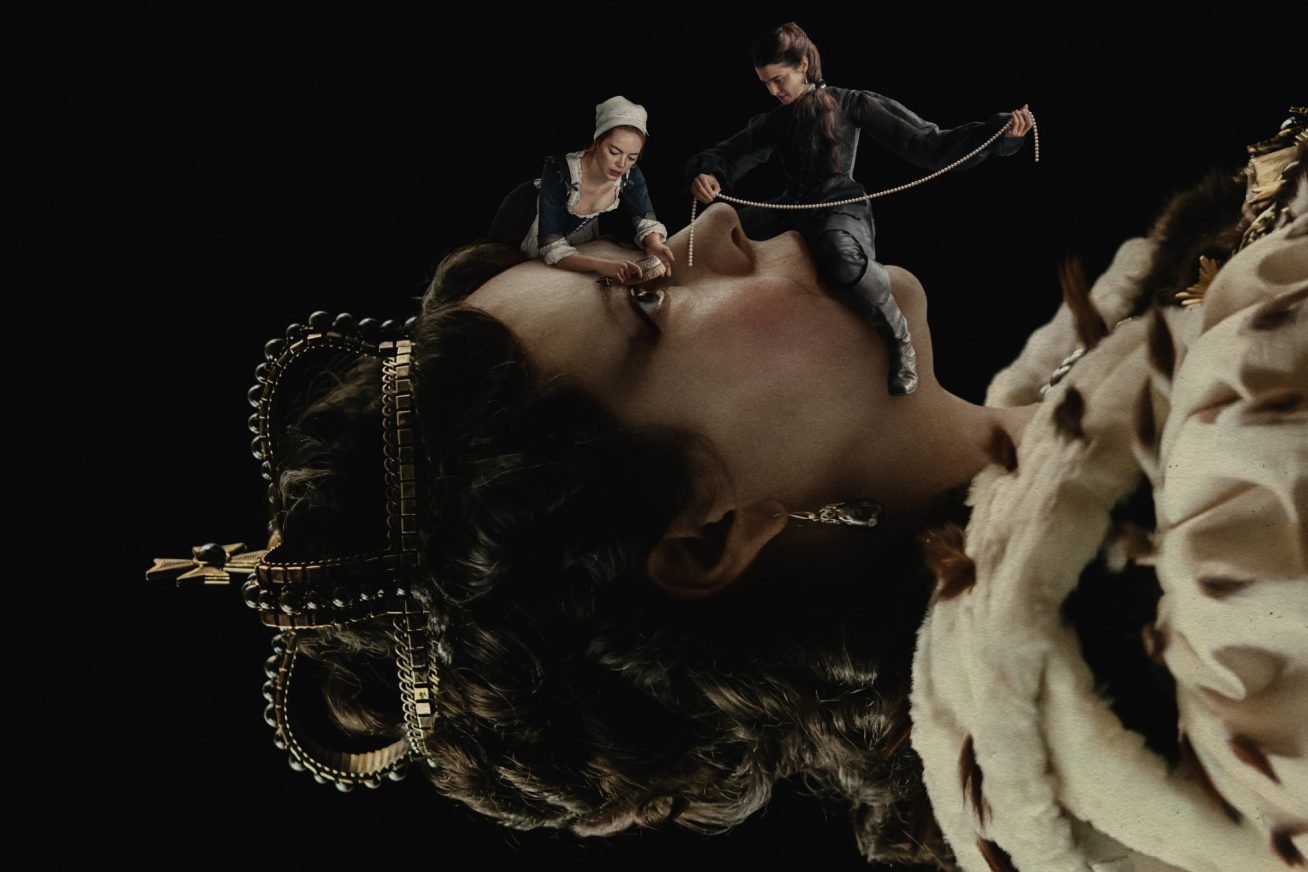In this still from The Favourite, a queen in an 18th-century crown and gown lies horizontally over a background. We see her body from the shoulders up. Over her face, two tiny women in 18th-century dress climb over her face, and look as though they're trying to tie her up.