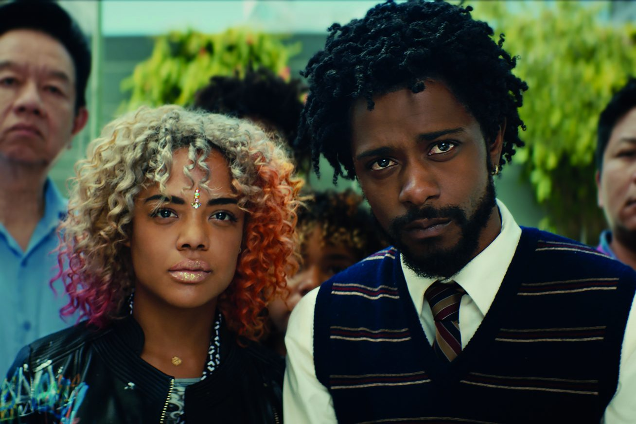 A young African American woman with multi-coloured hair stands next to a young, bearded African American male in a shirt, tie and sleeveless blazer. Both look into the distance beyond the camera in this still from Sorry to Bother You.