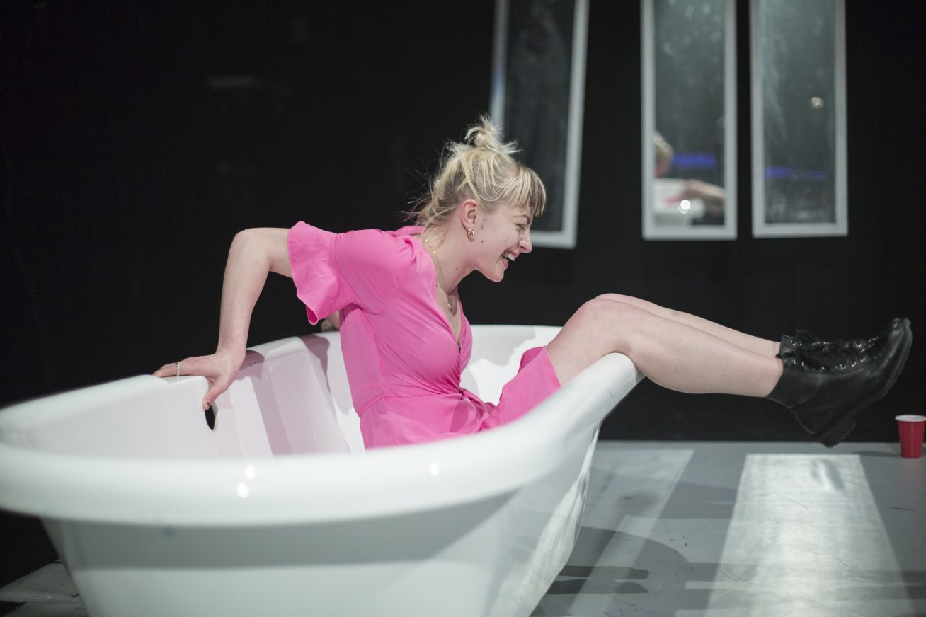 A woman in a pink dress sits in a bath tub with her legs dangling out the side and a big smile on her face