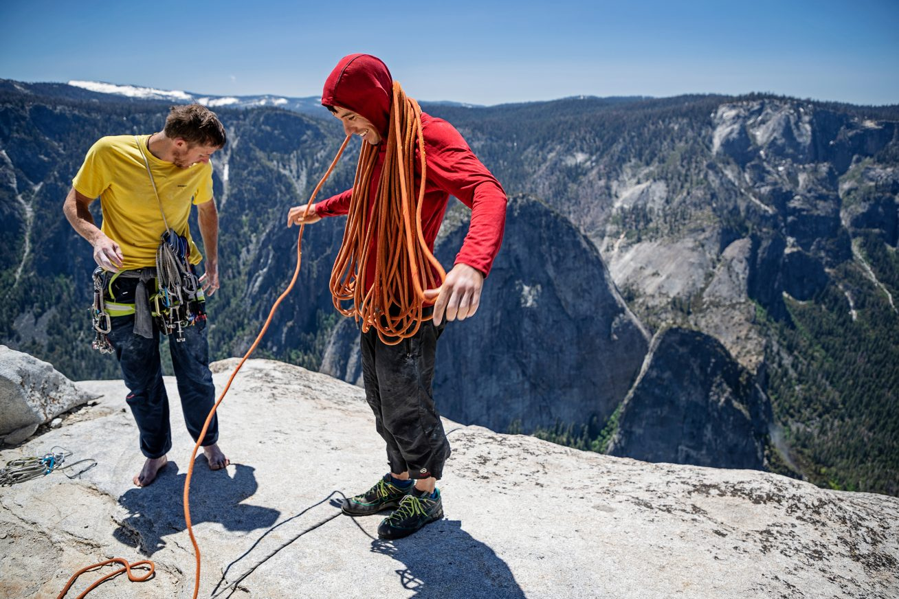 Two young men stand on the edge of a cliff, in the background is a blue cloud and another large cliff. On the left of the image, one of the men wears a yellow t-shirt, and on the right one wears a red hoodie. Together they unravel orange rope in this image from the documentary Free Solo.
