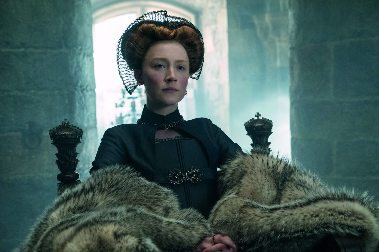 In a Renaissance court room, a young, redheaded queen sits on a wooden throne. She wears an intricate headpiece, an elegant blue outfit, and around her arms is a big, thick fur coat. Behind her is a window, through which streams a moody light in this still from Mary Queen of Scots.