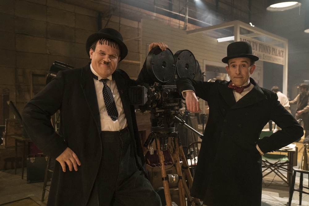 Two actors resembling the iconic Stan and Ollie lean comically up against an old-fashioned movie camera. Their wear bowler hats, and comically misfitting black and white suits.