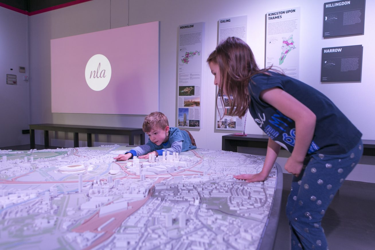 A child is engaged in an activity along with it's mother, pointing to a building on a map.