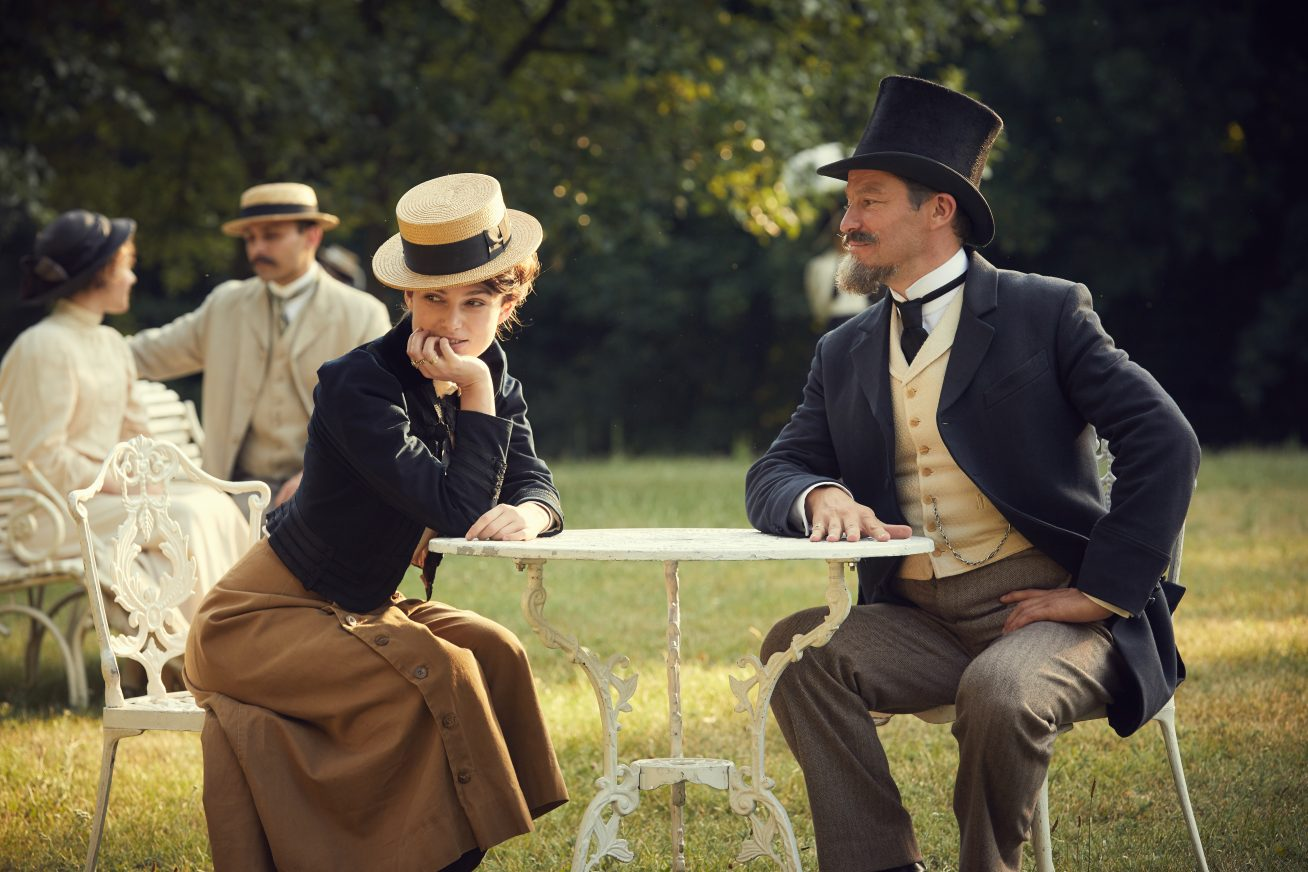 In a eighteenth century Parisienne park, a woman and man sit in fancy clothes and top hats in this still from Colette.