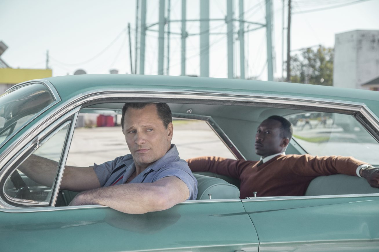 In a deserted looking industrial estate, two men sit in the foreground in a pretty turquoise American Cadillac. The white man in the driver's seat drapes his arm out the window and glances backwards. The black man in the back seat reclines in his seat with his arms spread across the seats next to him. This image is from the film Green Book.
