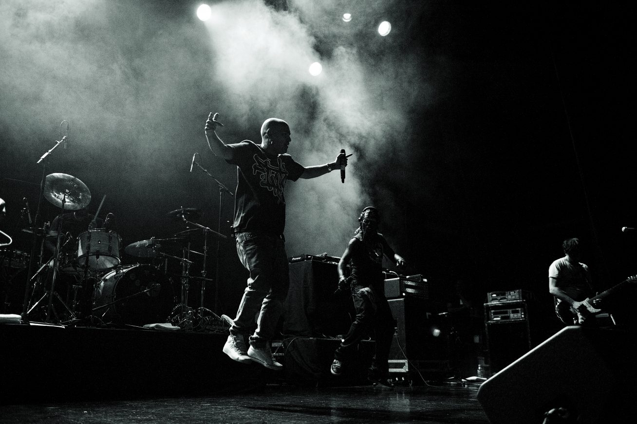 A black and white image of Asian Dub Foundation performing on stage. In the background there is smoke, and in the foregorund, the lead singer jumps in the air.