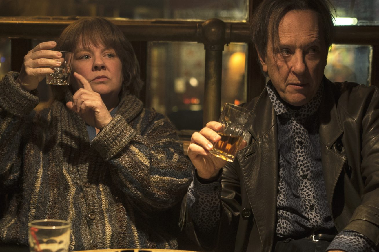 In a run down looking pub, two disheveled prople sit at a bar. On the left is a woman who holds up her tumbler, and points at it as though asking for a refill. On the right, a man with a long fringe also holds out his glass, at a slightly tipsy looking angle. This picture is from the film Can You Ever Forgive Me?