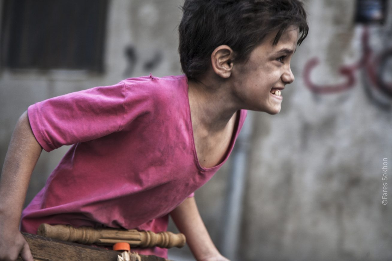 A young boy leans across this still from the film Capernaum. He wears a lose, v-neck pink shirt, and looks quite thin. His skin is covered in a sort of muddy dirt. He has dark hair, and his expression looks like a mix of desperation and pain.