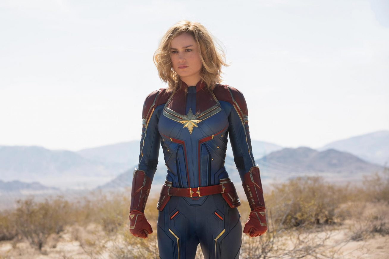 A blonde woman stands with clenched fists in a vast open field. In the background there are distant hills. She wears a dark blue and red superhero suit in this still from Marvel Studios' CAPTAIN MARVEL.