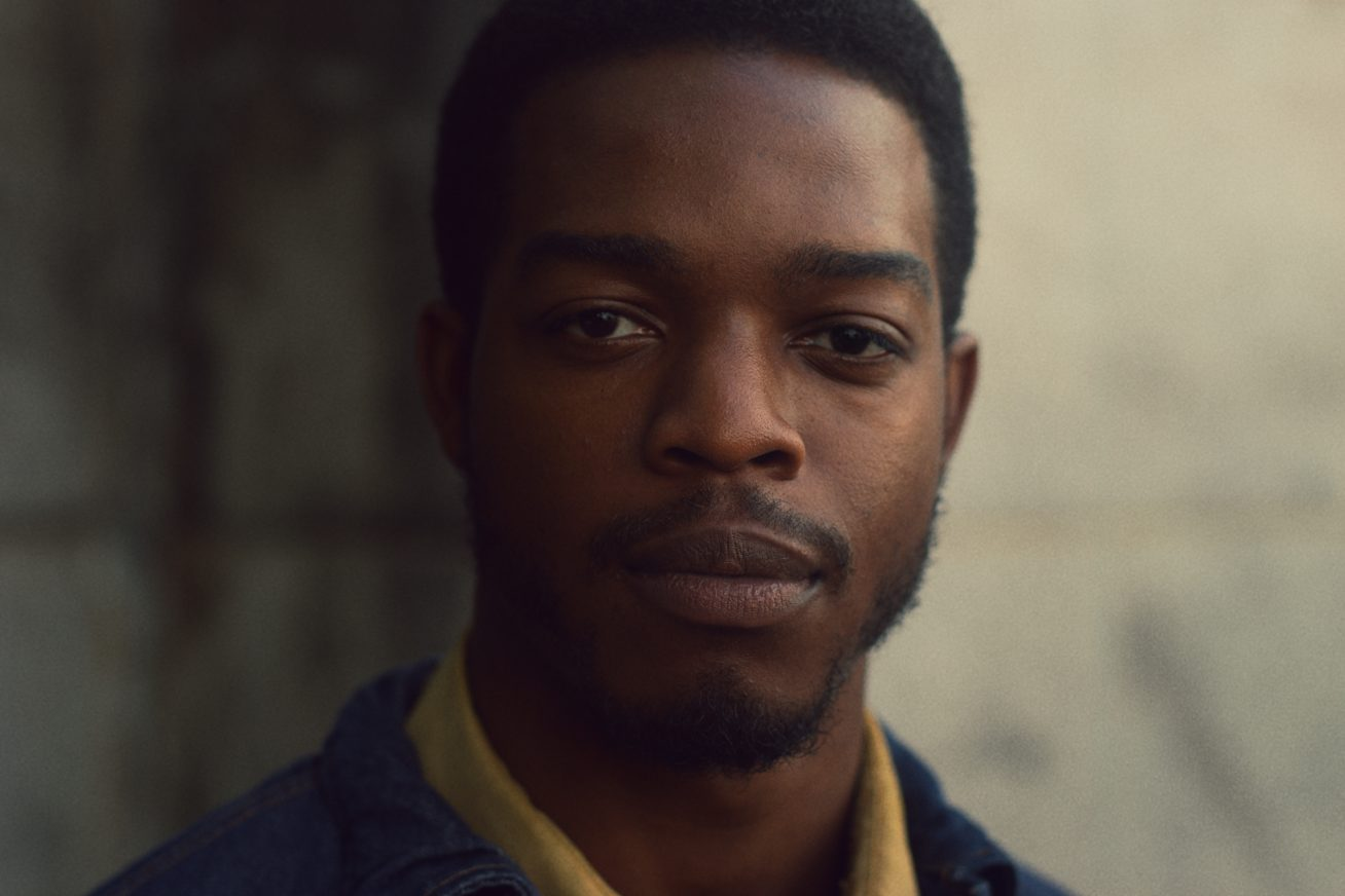A young African American male stands before the camera with short, natural hair, and a short, well-groomed beard. On his shoulders we see a yellow shirt and a brown jacket. Behind him is a light, yellow-coloured wall in this still from If Beale Street Could Talk.