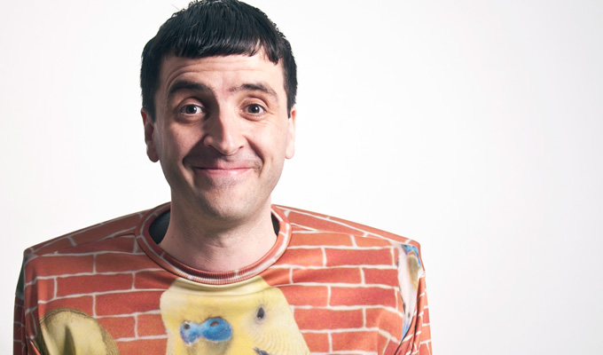 A man with a squiffy hair cut stands in front of us white background with a funny grin on his face. He wears a most bizarre t-shirt that has a red-brick wall pattern on is, and the face of a bright yellow budgie. This picture is a promotional shot for Knock2Bag Stand Up Comedy Night.