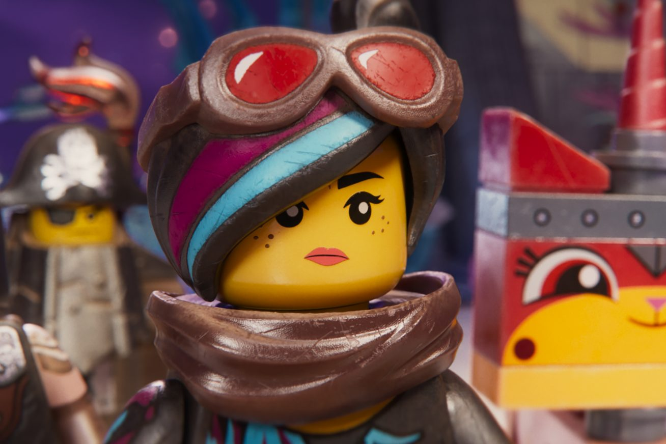 Four colourful LEGO figurines strut towards us, as if about to go on a mission. On the left, is a figurine that looks like Batman. In the middle is a female figurine who has red goggles on her forehead. On the right, there is a figurine that has a square cat-like face. This animated image is a still from THE LEGO MOVIE 2.