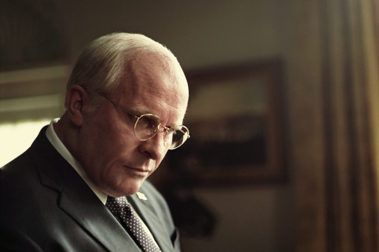 A man resembling American ex vice president Dick Cheney stands in the White House's oval office. He wears a light grey suit, and his hair is receding and white. He gazes downward thoughtfully, with silver framed glasses on the bridge of his nose. This image is from the film Vice, out in cinemas Friday 25 January.