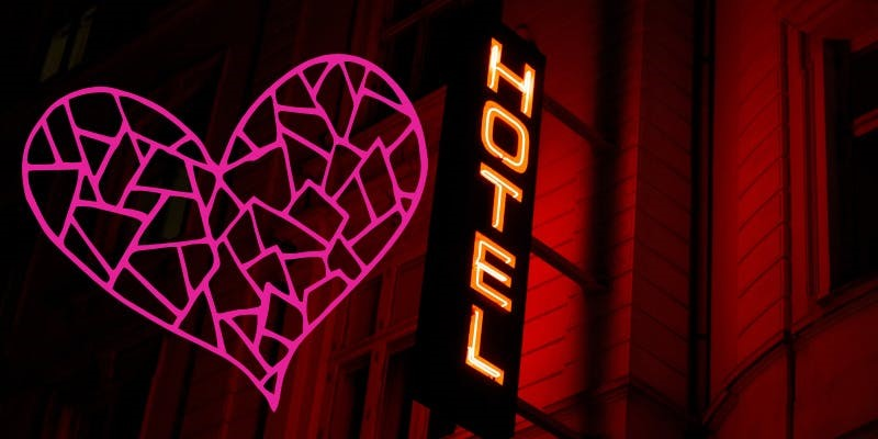 A shot of a wall with two bright neon signs bolted to it. One is of a fractured pink heart, the other spells out the word hotel, and casts a deep red light on the wall. The image is from Heartbreak Hotel Festival.