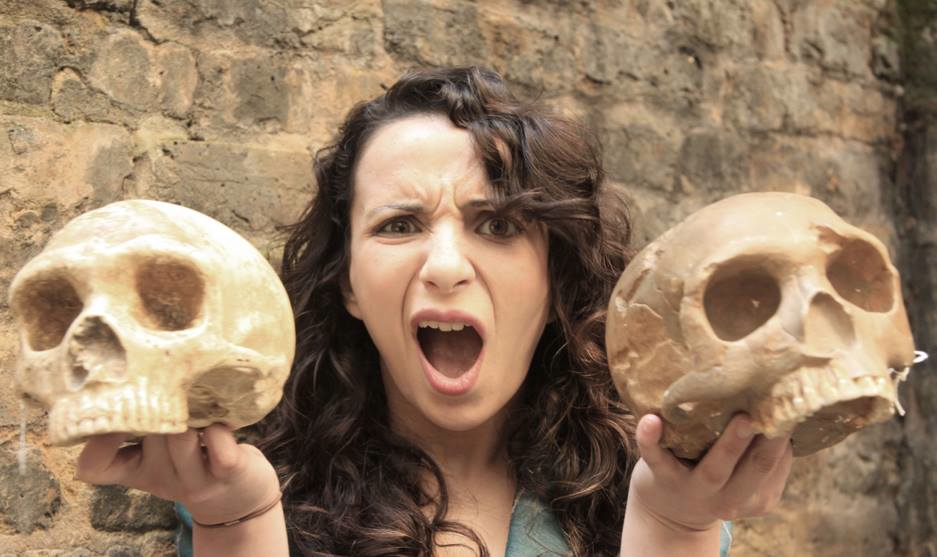A woman pulls a funny face as she holds two skulls up to the camera