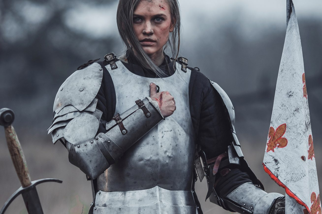 A woman wears armour as if she's in battle, and holds her fist over her heart