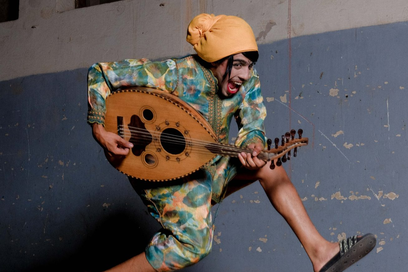 A person jumps in the air whilst smiling and playing a guitar-like instrument