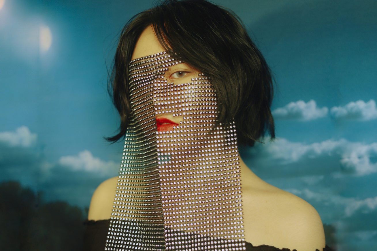 A woman poses with a mesh vail over her face